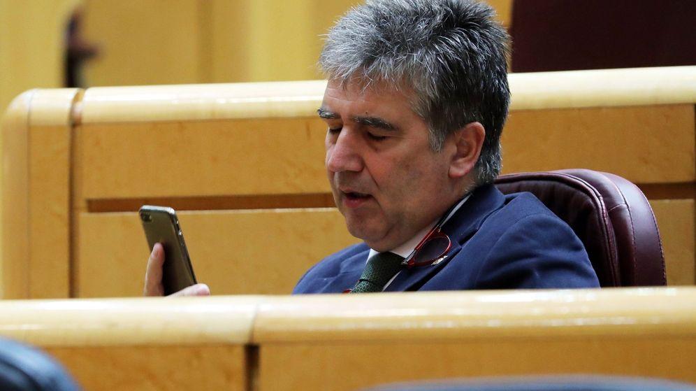 Foto: Cosidó mira el móvil con el que envió el wasap maldito. (EFE)