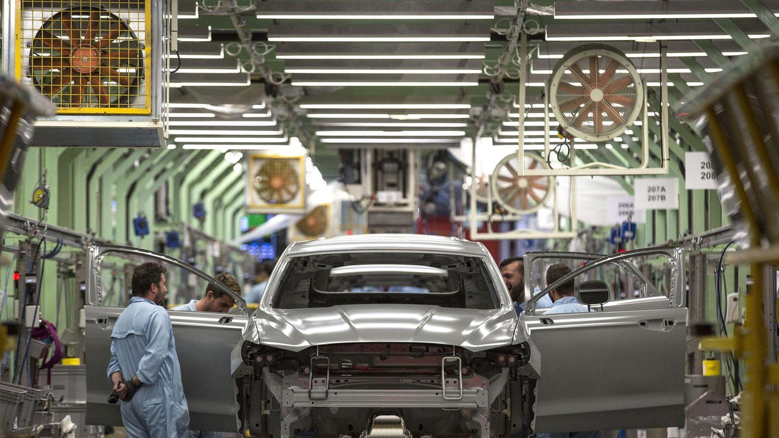 Foto: Trabajadores revisan una carrocería en la cadena de montaje de Almussafes. (EFE)
