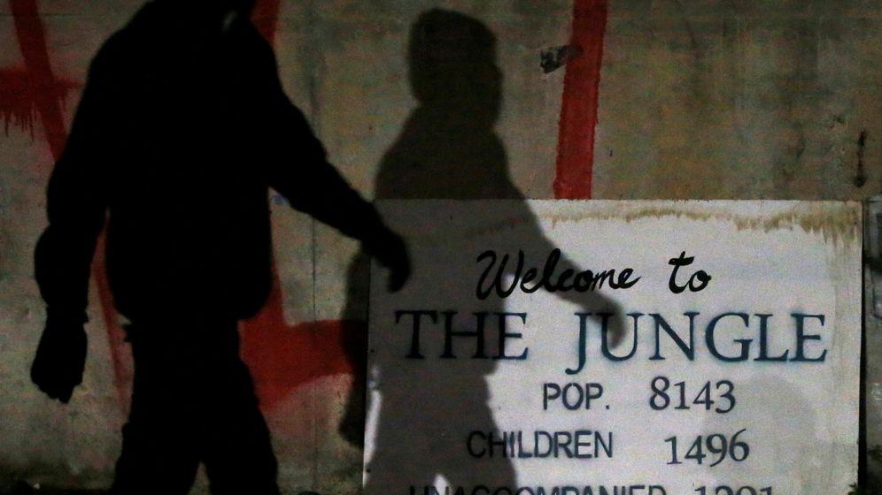 Foto: La sombra de un inmigrante frente a un cartel de bienvenida a la Jungla, el campo improvisado en Calais, poco antes de su desmantelamiento en octubre de 2016. (Reuters)