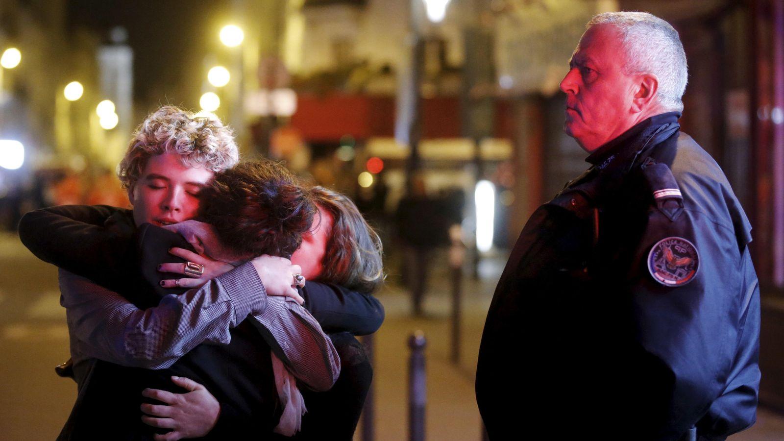 Foto: Varias personas se abrazan en las calles de París tras los atentados. (Reuters)