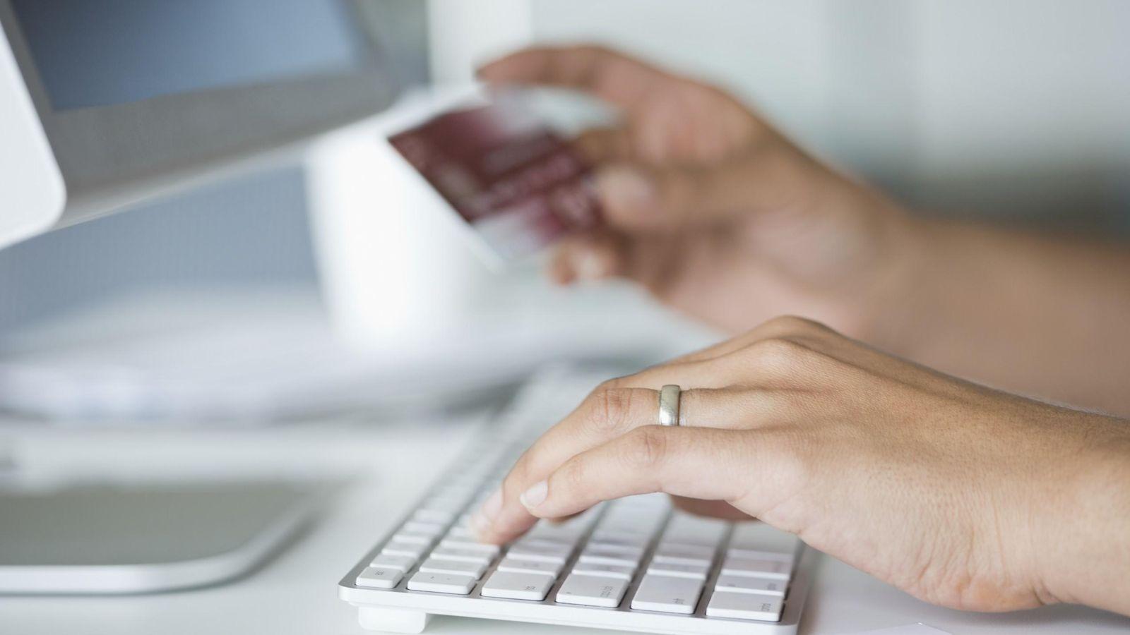Foto: Una mujer utiliza su tarjeta de crédito para efectuar gestiones bancarias en internet. (Corbis)