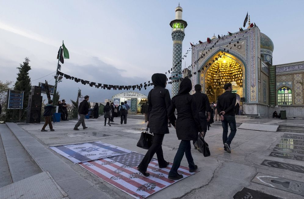 Foto: Iraníes pasan sobre una bandera de EEUU y otra de Israel en la entrada de una mezquita en el norte de Teherán. (Reuters)