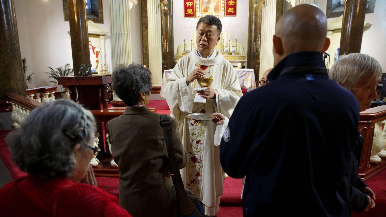 Un sacerdote da la comunión durante una misa en la Iglesia de San José, en Pekín. (Reuters)