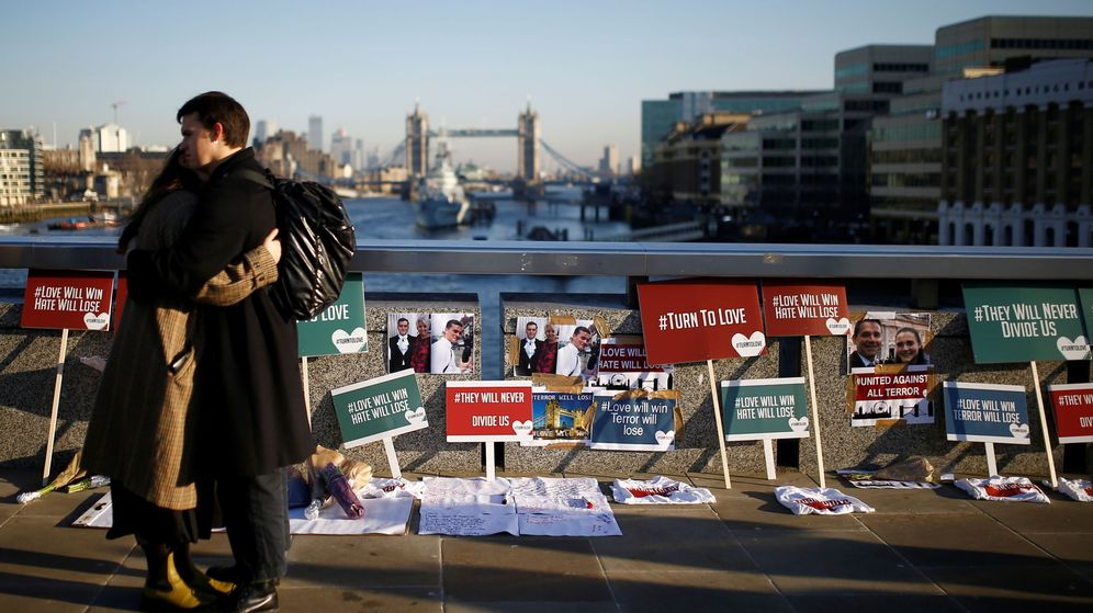 Foto: People embrace each other in front of placards and tributes to victims on london bridge in london