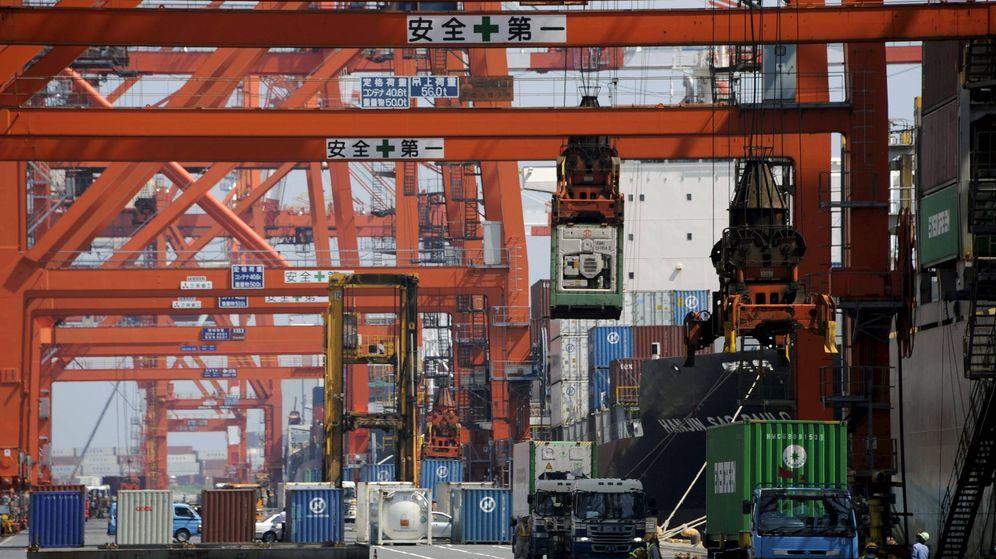 Foto: Trabajadores cargan contenedores en un barco carguero en un puerto de Tokio (Japón). (EFE)