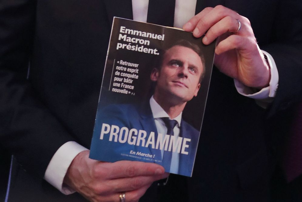 Foto: Emmanuel Macron sostiene un ejemplo de su programa en la rueda de prensa en la que lo ha presentado (Reuters)