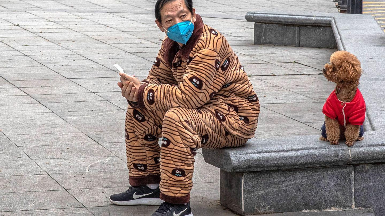 Un hombre protegido con una mascarilla descansa de un paseo con su perro en Wuhan (China), este lunes. (EFE)
