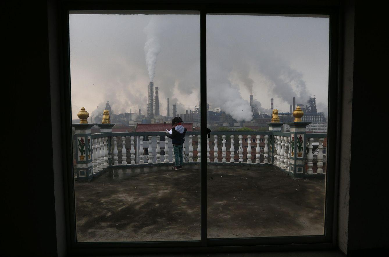 Foto: Una niña lee en el balcón de su casa mientras columnas de humo se elevan sobre una planta de acero en Quzhou, en la provincia china de Zhejiang. (Reuters)