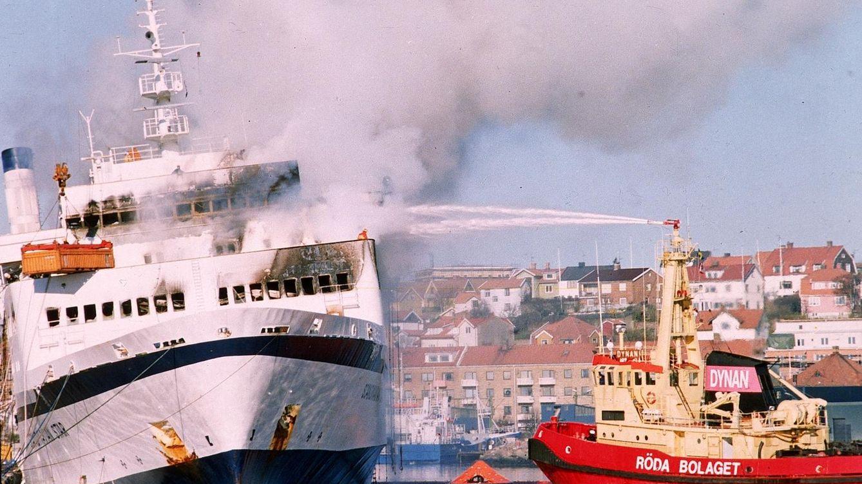 Foto: Un equipo de bomberos apaga el fuego del Scandinavian Star, ya de día.