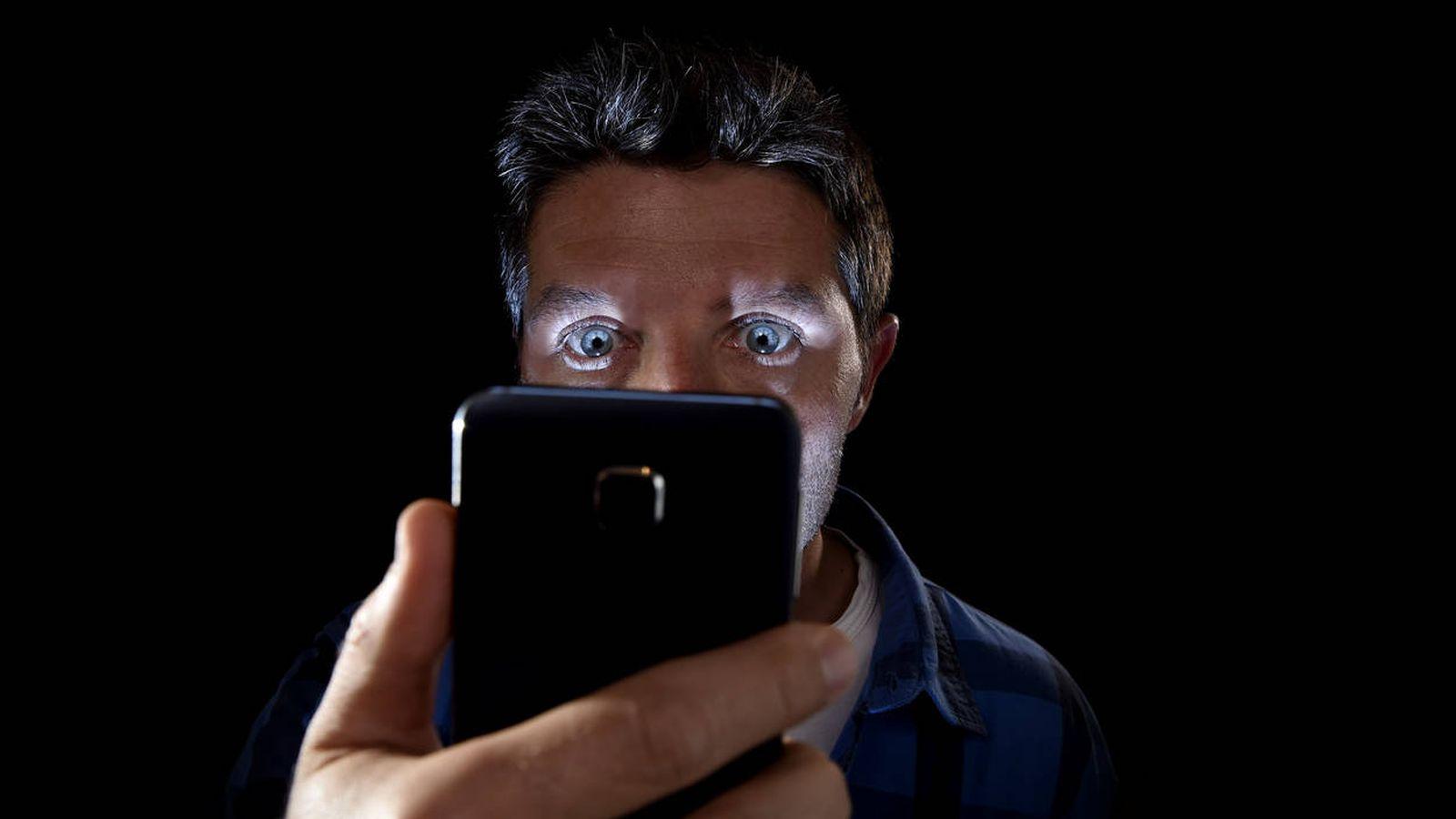 Foto: Un actor de imágenes de recurso mira intensamente a la pantalla de su móvil (iStock)