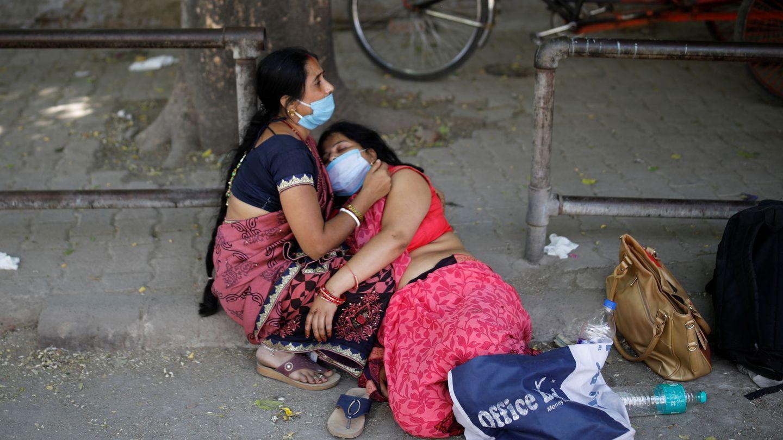 Unas mujeres lloran la muerte de un ser querido por coronavirus a las afueras de un crematorio en Nueva Delhi. (Reuters)
