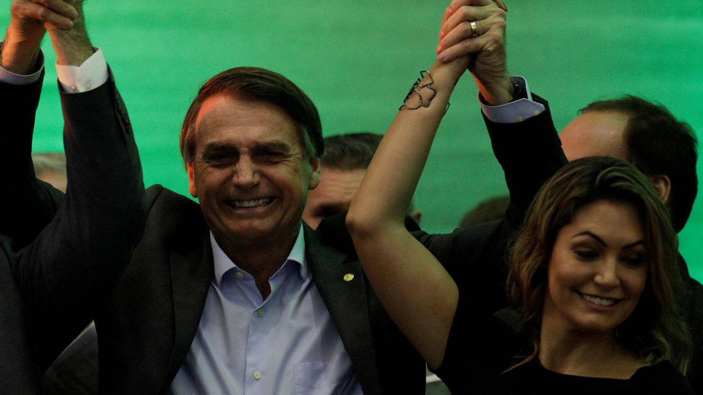 Bolsonaro levanta el brazo de la victoria junto a su esposa. (EFE)