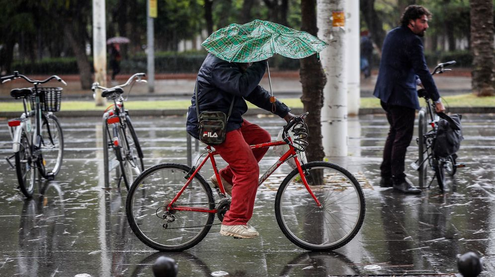 Foto: Una persona circula en bicicleta mientras intenta resguardarse de la lluvia con un paragua en Sevilla. (EFE)
