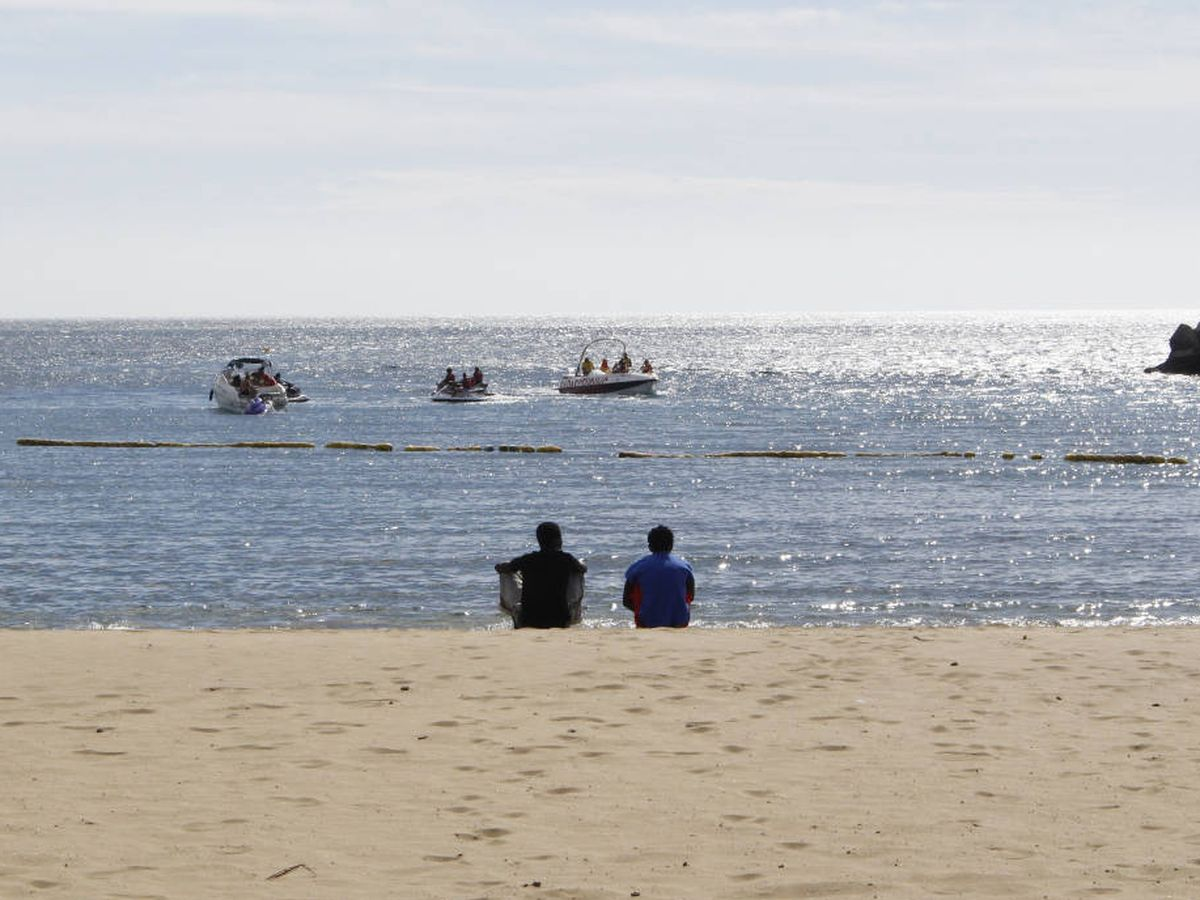 Foto: Dos migrantes miran el horizonte en la playa de Puerto Rico, sur de Gran Canaria. (A. Alamillos)