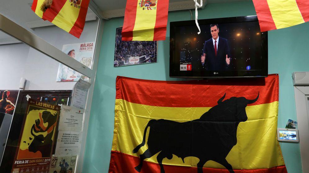 Foto: Banderas españolas al lado de una pantalla de televisión con la imagen de Pedro Sánchez en el debate. (Reuters)