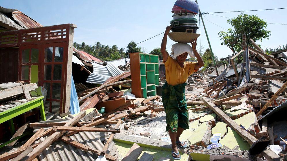 Foto: Una mujer carga con sus pertenencias entre los escombros en el norte de la isla de Lombok (Indonesia). (EFE)