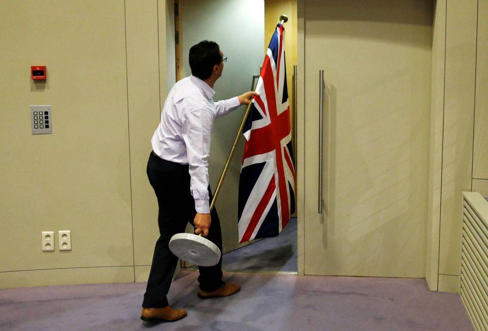Foto: Un trabajador saca una bandera británica tras una conferencia de prensa en Bruselas. (Reuters)
