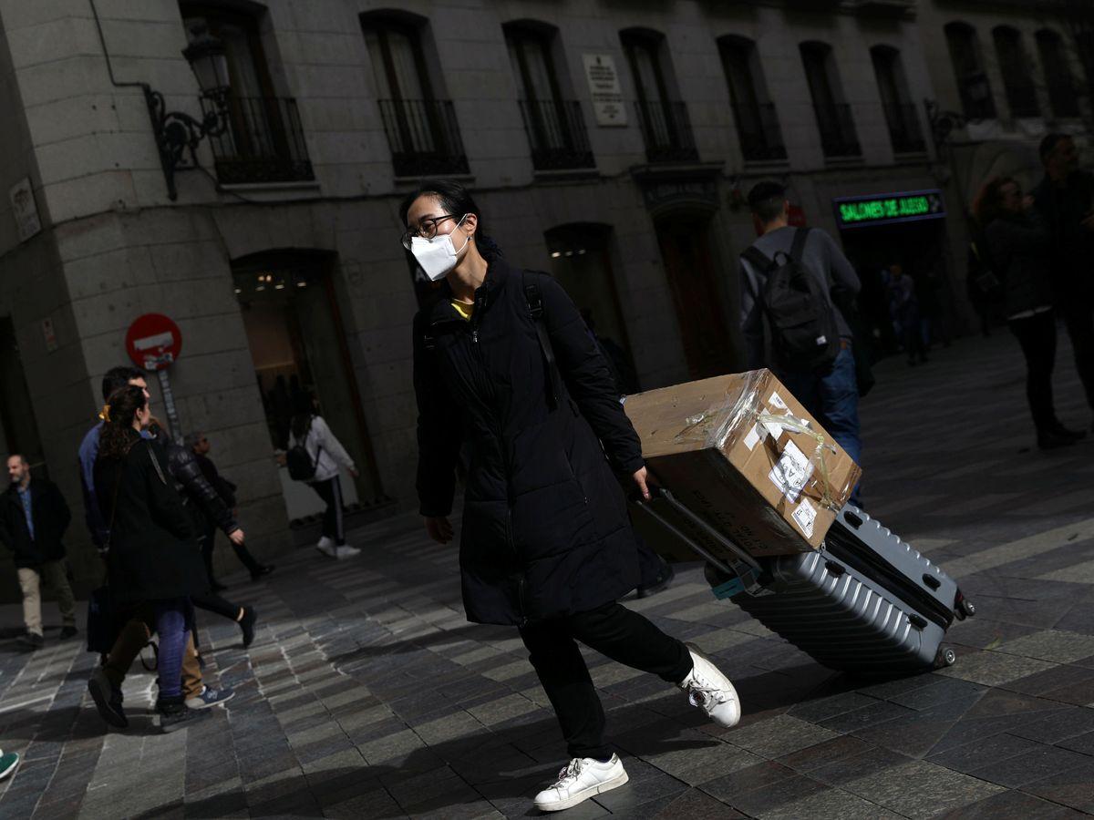 Foto: Una mujer con mascarilla arrastra su maleta en Madrid. (Reuters)