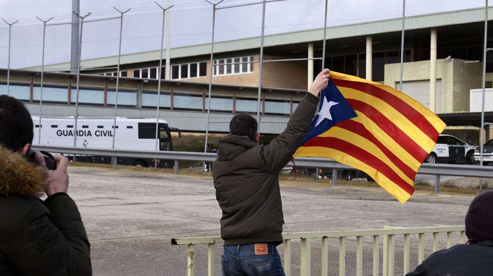 Foto: Un hombre ondea una estelada a la llegada del autobús con los presos del procés a Soto del Real. (EFE)