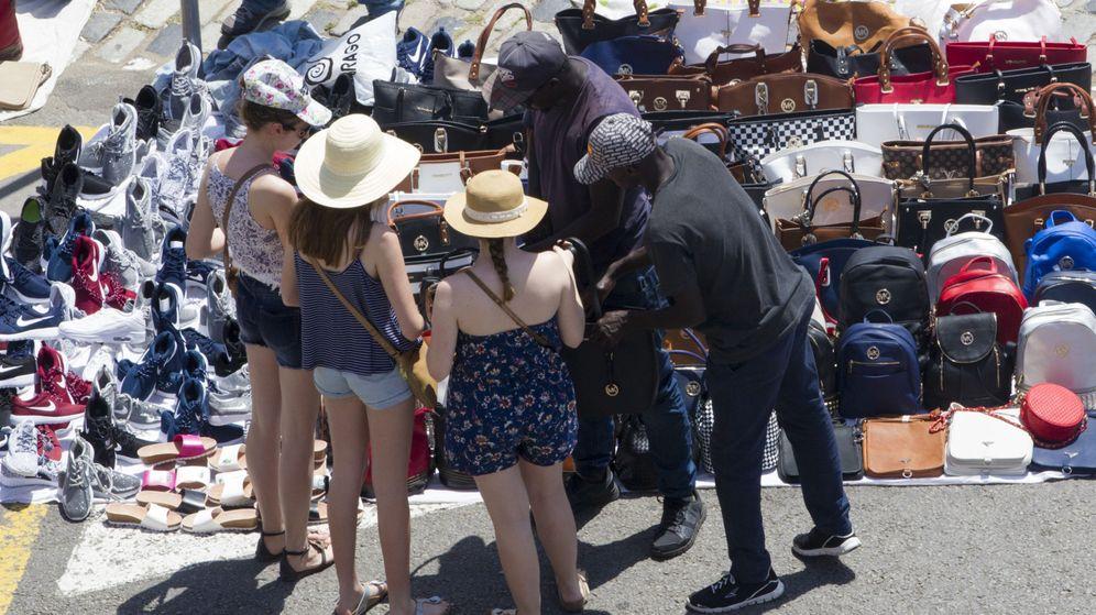 Foto: Venta ambulante ilegal en Barcelona a varias turistas. (EFE)