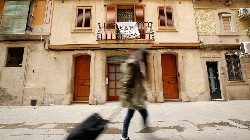 Foto: Una joven sostiene su maleta frente a una pancarta contra Airbnb (Reuters)