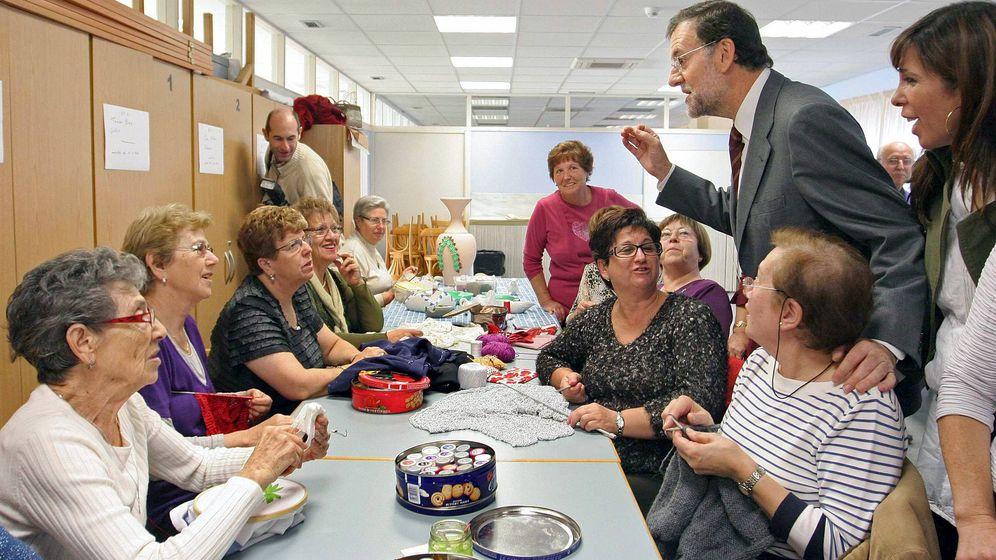 Foto: Mariano Rajoy conversa con un grupo de mujeres durante una visita a una residencia de ancianos. (EFE)