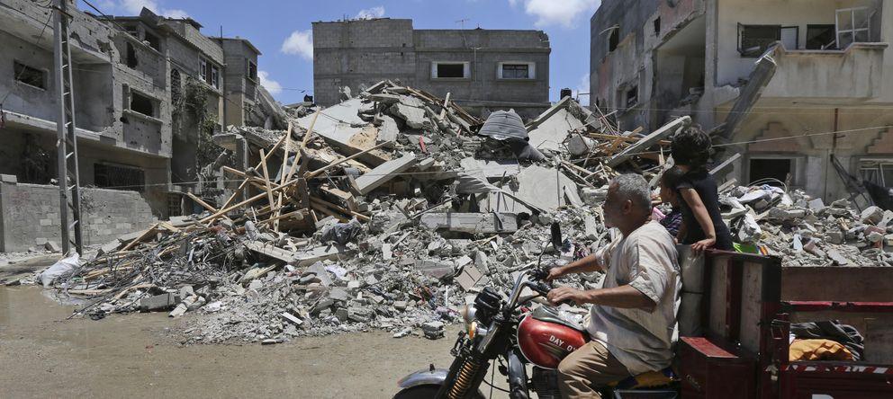 Foto: Palestinos conducen entre escombros de edificios atacados por la aviación israelí en Rafah, al sur de la Franja (AP).