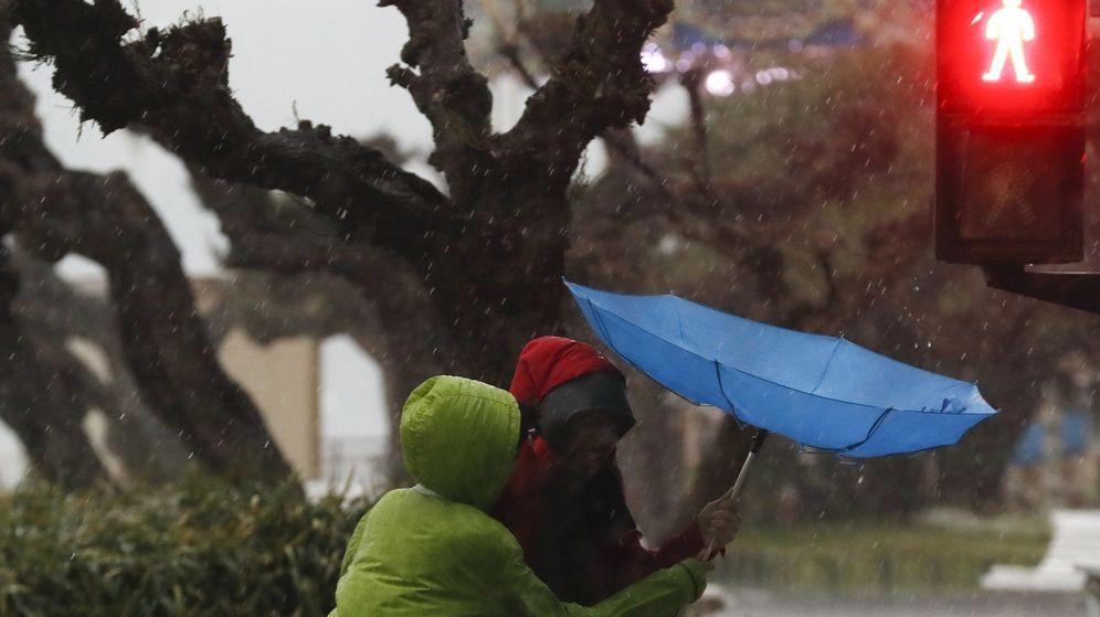 Foto: Unos turistas se protegen con un paraguas e en el paseo de la Concha de San Sebastián. (EFE)