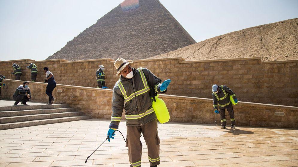 Foto: Varias personas desinfectan las inmediaciones de las pirámides de Guiza. (EFE)