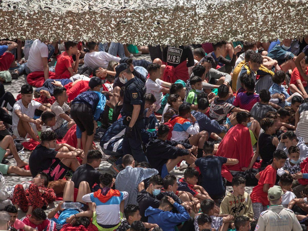 Foto: Decenas de migrantes en un polígono industrial de Ceuta. (EFE)
