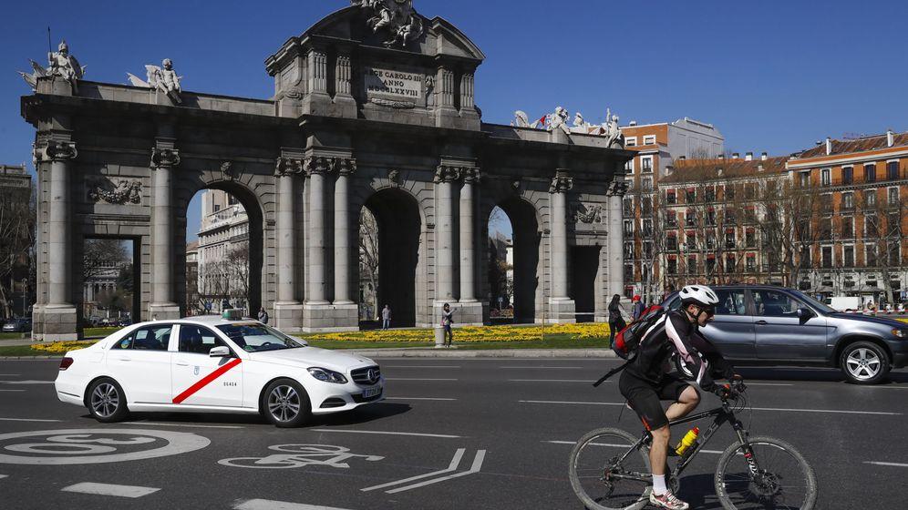 Foto: Un ciclista, a su paso por la Puerta de Alcalá. (EFE)