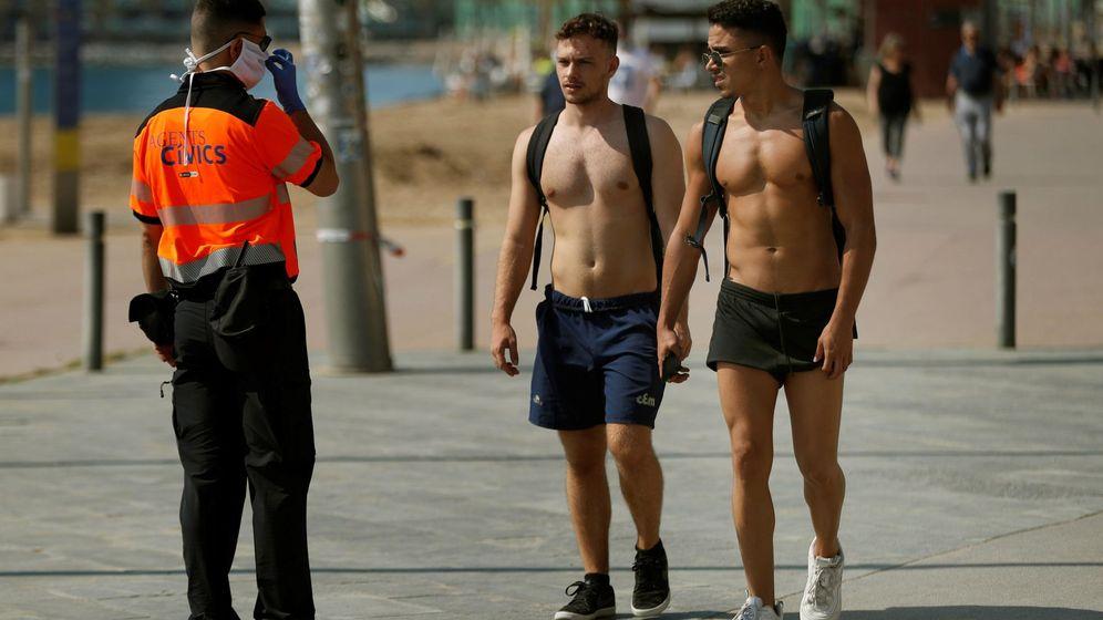 Foto: Un agente realiza indicaciones a dos jóvenes en la Barceloneta. (EFE)