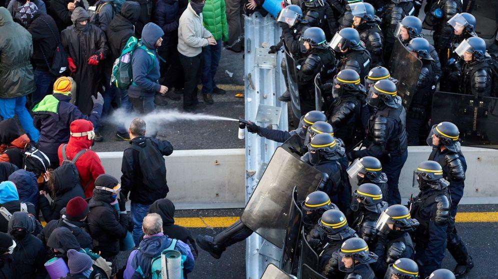 Foto: Antidisturbios franceses desalojan a los manifestantes que bloquean el paso fronterizo de la autopista AP-7. (EFE)