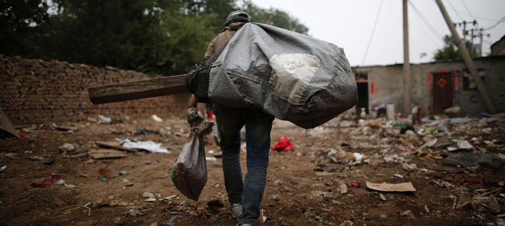 Foto: Un recolector de basura carga con un saco lleno de restos de equipos electrónicos (Reuters).