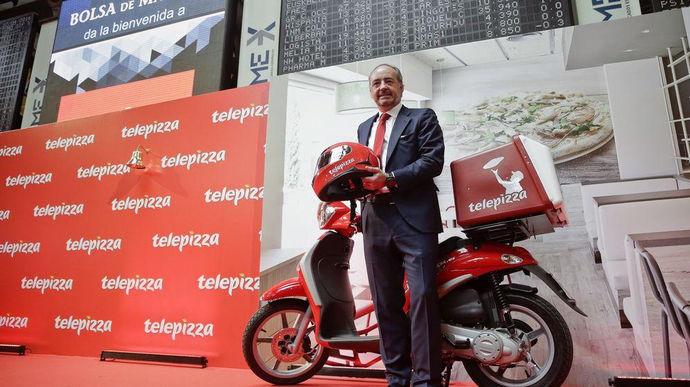 Foto: El presidente de Telepizza, Pablo Juantegui, posa en el parqué madrileño junto a una de las típicas motos de reparto. (EFE)