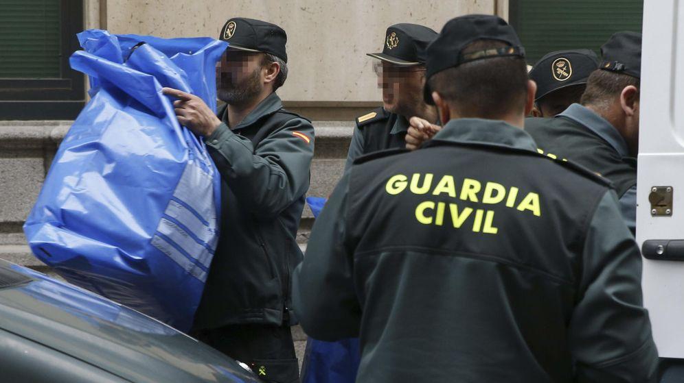 Foto: Agentes de la Guardia Civil trasladan los efectos personales de los once detenidos. (EFE)