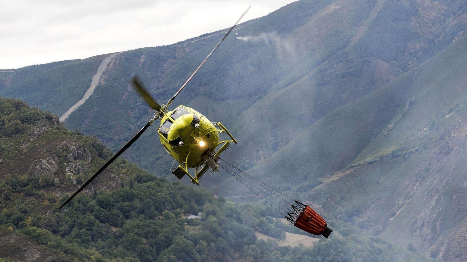Foto: Un helicóptero descarga agua en un incendio forestal. (EFE)