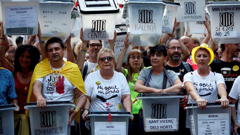 Manifestantes portan urnas en Barcelona con el nombre del municipio al que pertenecen. (EFE)