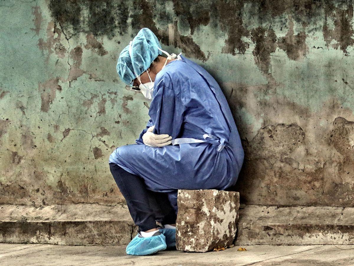 Foto: Una mujer con un traje de bioseguridad descansando. (EFE)