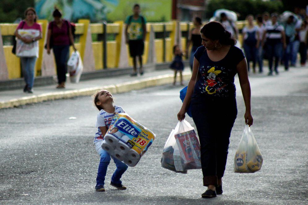 Foto: Un niño venezolano carga con un paquete de papel higiénico al cruza con su madre el Puente Simón Bolívar, que une Venezuela y Colombia (Reuters).