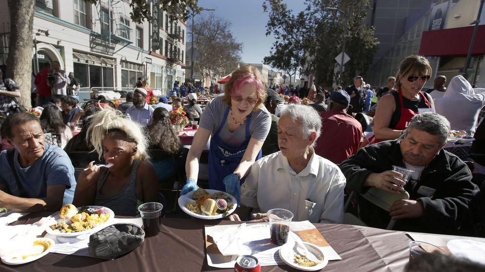 Foto: Una voluntaria entrega un plato durante una comida de Acción de Gracias para personas sin hogar y menos afortunadas. (EFE)