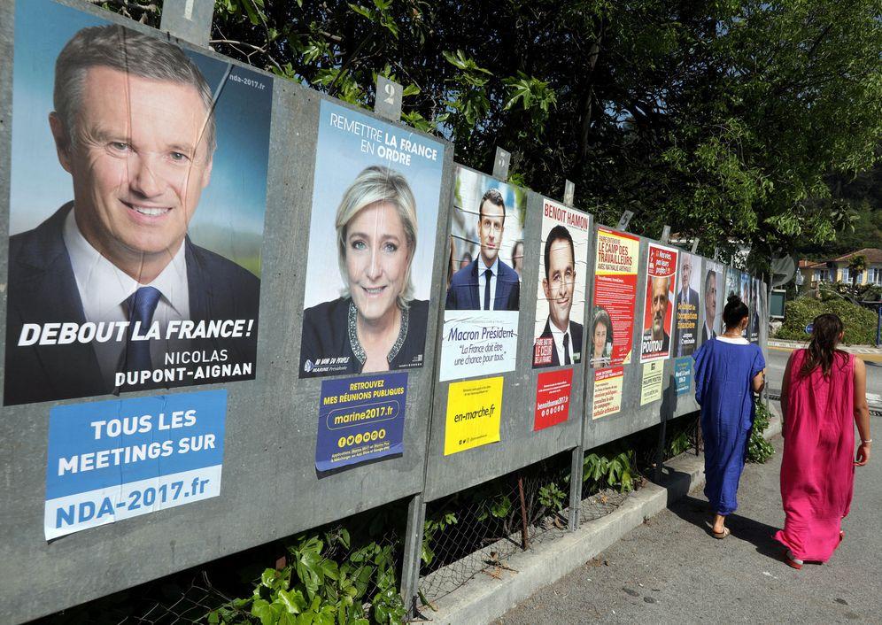 Foto: Dos mujeres pasan por delante de un muro lleno de carteles electorales en Saint André de la Roche, cerca de Niza, el 10 de abril de 2017. (Reuters)