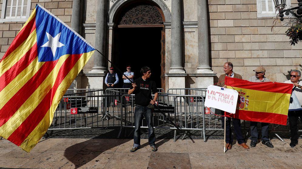 Foto: Un joven ondea una bandera independentista junto a un grupo de hombres con una bandera de España a las puertas del Palau de la Generalitat. (Reuters)
