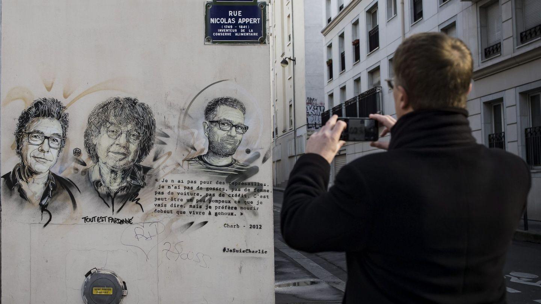 Un hombre fotografía una pintada en la que aparecen los dibujantes asesinados en la sede de 'Charlie Hebdo'. (EFE)