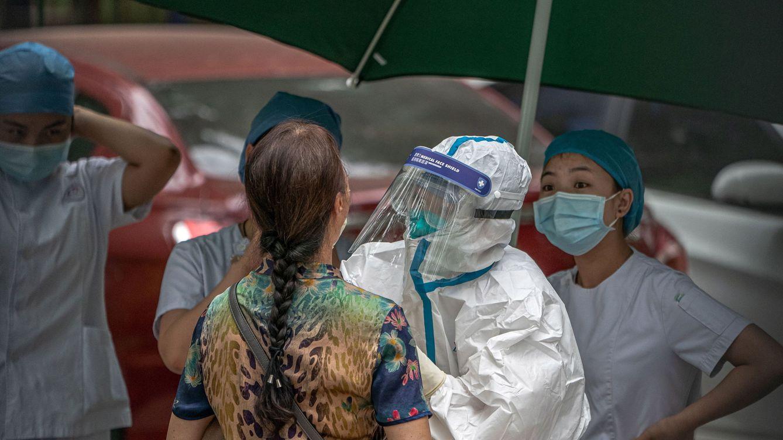 Foto: Un trabajador sanitario toma una muestra a una mujer (EFE)
