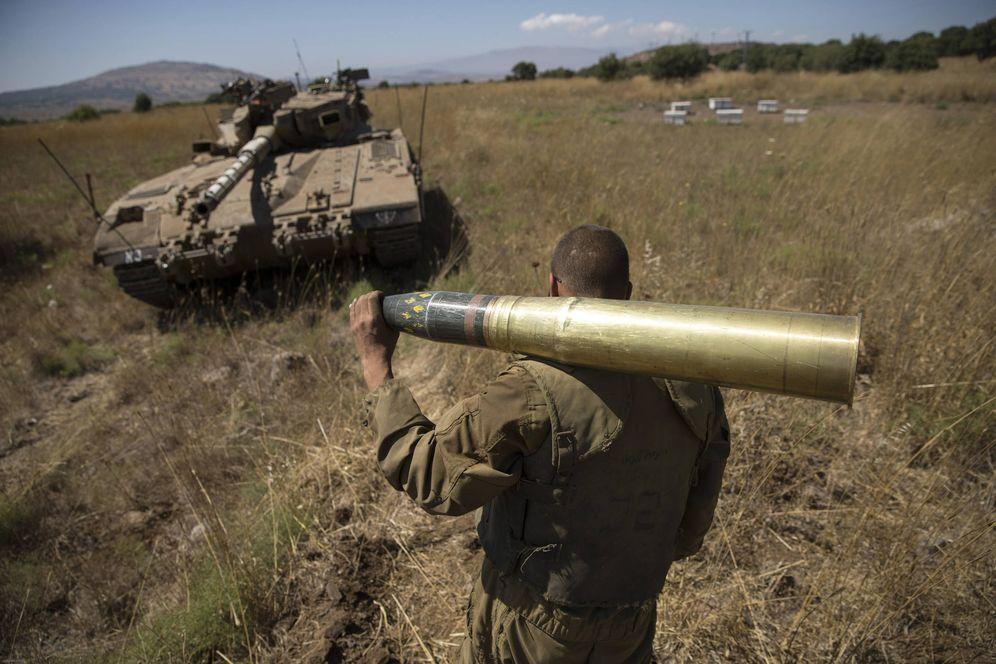 Foto: Un soldado israelí carga con un proyectil cerca de Alonei Habashan, en los Altos del Golán. (Reuters)