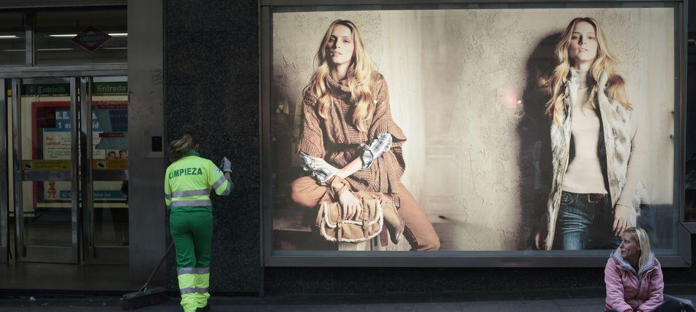 Foto: Una mujer pide limosna y otra barre la calle junto a unos grandes almacenes en Madrid (Reuters)