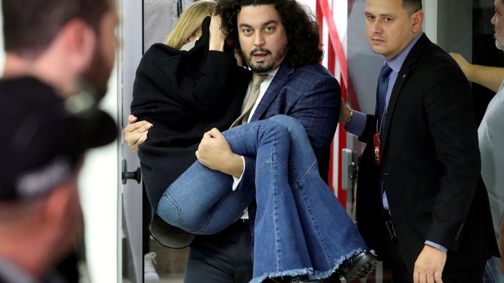 Foto: El abogado de Najila Trindade saca en brazos a la joven tras declarar en comisaría. (Reuters)