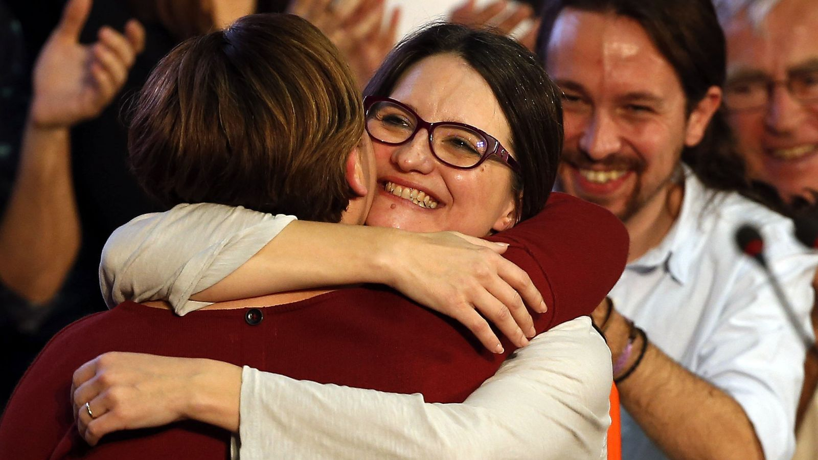 Foto: Colau y Oltra abrazándose en presencia de Iglesias. (EFE)
