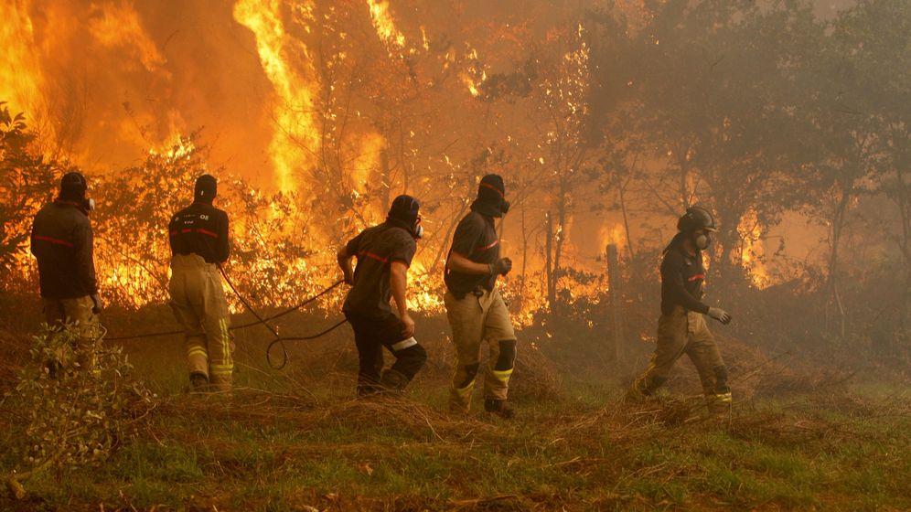 Foto: Operarios de los servicios de extinción de incendios trabajan en la zona de Zamanes, Vigo. (EFE)